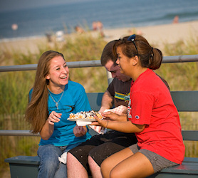 Students eating pastries by the beach.