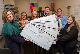 students posing with checks